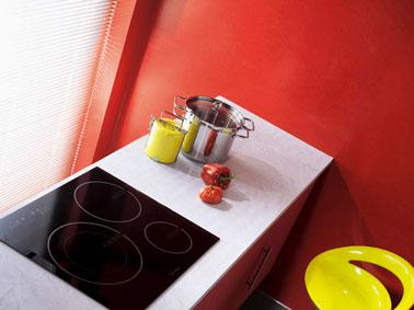 Façades meubles bas de l'espace cuisson d'une petite cuisine peints en rouge vif, sur les murs une peinture effet béton couleur rouge en rappel, table à induction noir, plan de travail blanc apportent un contraste fort. Tabouret de bar jaune vif.