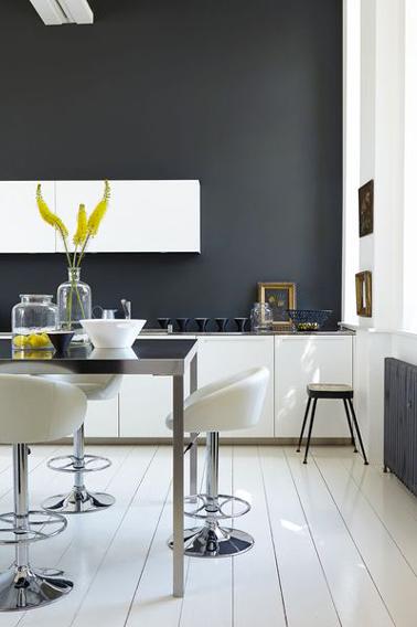Sur un des murs d'une cuisine blanche de style moderne, une peinture gris anthracite est une bonne façon de dynamiser l'ambiance en utilisant les contrastes.