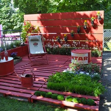 Sol terrasse bois en palettes aménagé dans un coin du jardin. sur les 6 palettes peintes en rose fushia, transat et bidon de recup formant le salon de jardin sont repeints dans la même couleur. Sur la claustra bois fermant l'espace, des jardinières en parpaing assorties