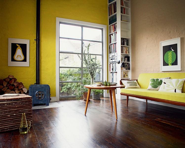 une peinture salon de couleur jaune sur un mur reveille les couleurs terre des autres murs