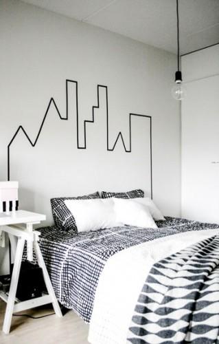 Sur les murs peints en blanc, la tête de lit est matérialisée avec un dessin reprenant les contours d'un château réalisé avec un ruban adhésif noir.