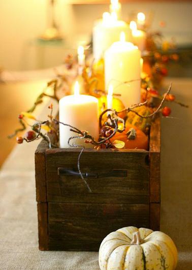 centre de table. composition avec bougies et branchages d'automne dans coffre bois