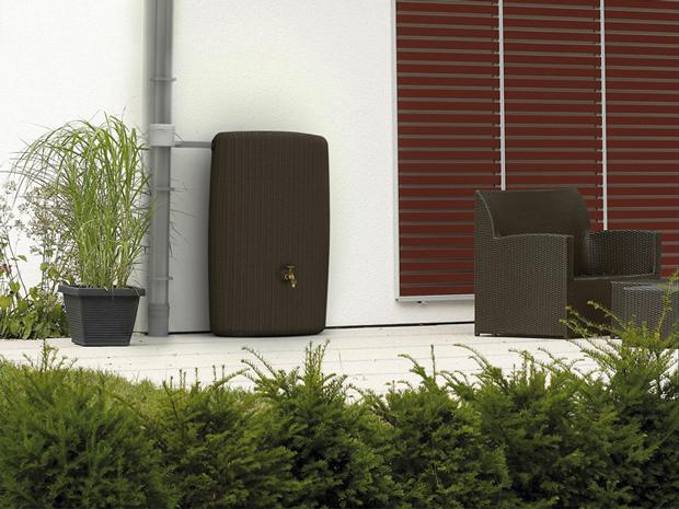 Un récupérateur d'eau de pluie de 300 litres de réserve finition tressée couleur chocolat assorti au solon de jardin