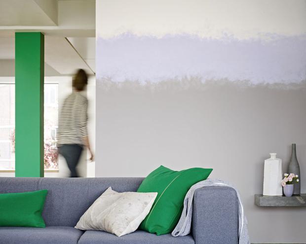 Pour agrandir ce salon ouvert, un dégradé de peinture couleur gris intense lavande et gris clair pour donner de la hauteur. Les coussins vert intense sur le canapé gris par un effet de contraste augmentent l'impression de volume dans le salon
