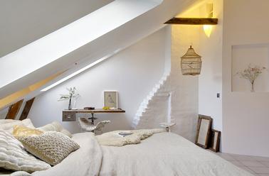 Une chambre beige et blanche aménagée dans un ancien atelier d'artisan. Pour construire une décoration épurée, les murs blanchis soulignent les poutres du plafond, le linge de lit beige renforce la douceur ambiante.