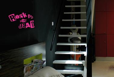 Pochoir lettre peint avec peinture fluo rose sur mur noir dans chambre enfant