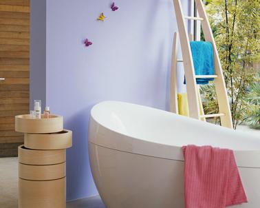 Déco salle de bain contemporaine. Autour de la baignoire design, peinture couleur lilas complétée de touches de couleurs vives avec les draps de bain rose bleu et jaune
