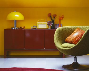 peinture jaune orangé dans salon, fauteuil coque vert et buffet bas rouge brique assorti au tapis de laine rond