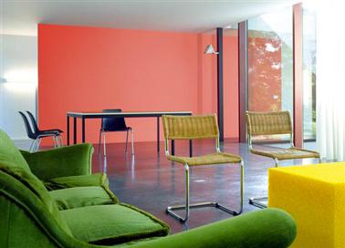 une peinture salon de couleur orange associé à un canapé couleur vert gazon et un sol en béton ciré gris anthracite, une harmonie de couleurs toniques pour la déco d'un salon contemporain