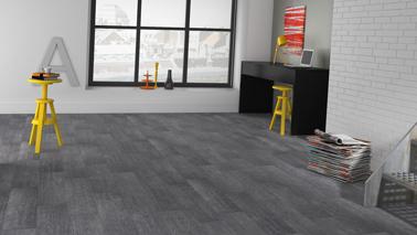 Imitation bluffante d'un sol béton esprit loft avec ce sol PVC lames auto-collantes couleur gris béton chez Saint Maclou