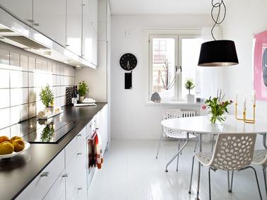 La blancheur immaculée des murs et du mobilier de cette grande cuisine permet de diffuser largement la luminosité dans la pièce. Une lumière naturelle donc qui vient magnifier la décoration subtile composée de plantes vertes et d'autres accessoires noirs faisant un écho direct au plan de travail en granit noir également.