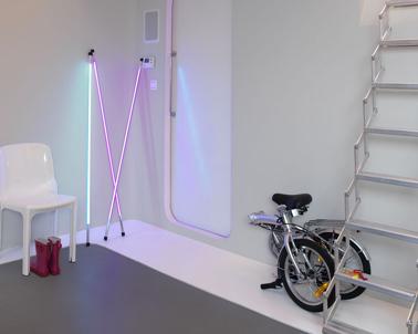 Déco entrée d'un appartement moderne avec mobilier contemporain, peinture gris pastel et pour éclairage des néons rose bonbon