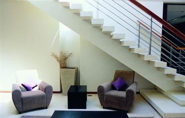 Une déco d'entrée et escalier d'une maison contemporaine qui mise sur le tout blanc et les éclairages indirects pour créer une ambiance feutrée