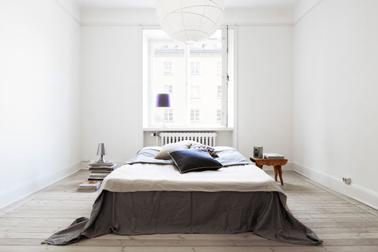 Pour gagner de la place dans une petite chambre, placer le lit au centre de la pièce, idéalement devant la fenêtre pour aérer l'espace