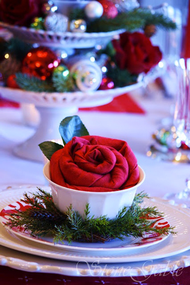 Serviette rouge pliée en forme de fleur posée dans coupelle blanche et décorée de feuillage vert