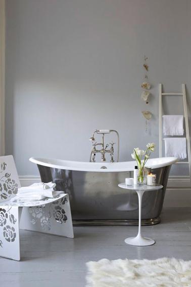 Salle de bain grise et blanc avec baignoire îlot finition étain, échelle en bois clair qui fait office de porte serviette posé sur mur gris pastel.