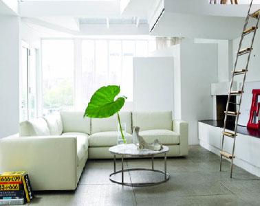 Bénéficiant d'un superbe plafond accueillant les pièces en mezzanine, la déco de ce salon design sait créer une ambiance cocooning autour du canapé de cuir blanc cassé.