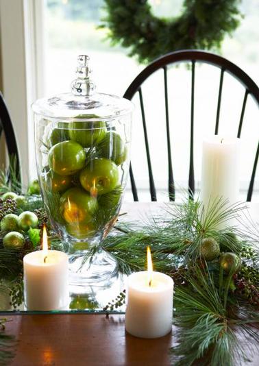 Centre de table de Noël vert et blanc à faire avec des petites boules de Noël vertes, des pommes vertes, des bougies blanches disposés dans une coupe en verre posée sur un miroir