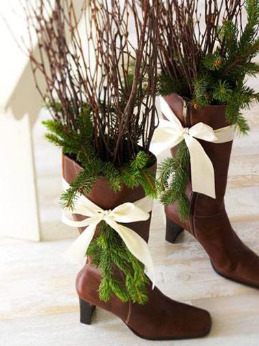 bottes de cuir customisées en décoration de Noël dans l'escalier avec des branchages de bois sec, des branches de sapin et du ruban blanc noué dans le haut des bottes