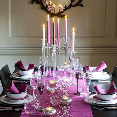 Déco table Noël couleur noir et rose fushia. Sur la table noire chemin de table en coton rose fushia, bougeoirs en verre et argent