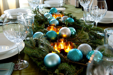 Centre de table de Noël composé de branche de sapin, de boules de Noël bleu turquoise brillantes et mates