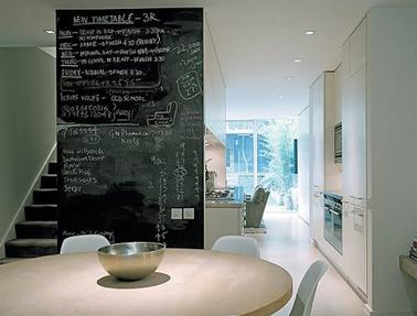 Espace cuisine salle à manger conçu par le cabinet d'architecture Alan Higgs Architects avec une cloison de séparation peinte avec peinture à tableau noir