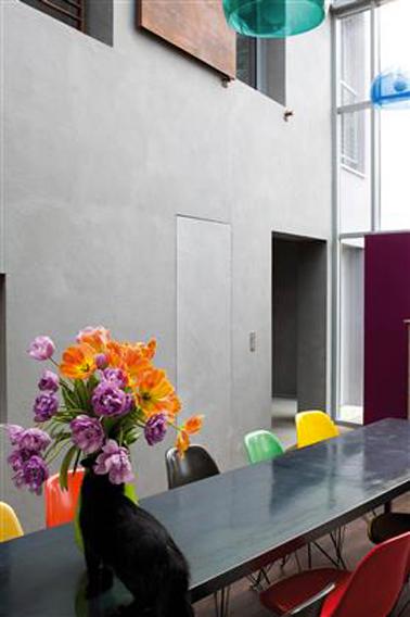Le gris et noir pour la décoration de cette salle à manger d'une architecture moderne. Les chaises de couleur vives et les suspensions dynamise l'ensemble