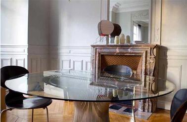 Peinture gris perle pour la déco d'une salle à manger qui mélange les styles avec une cheminée en marbre marron une table en verre mderne et des chaises de styles scandinaves noires