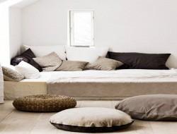 deco chambre zen dans loft. une decoration interieure épurée avaec grand lit, coussin de sol couleur lin et taupe
