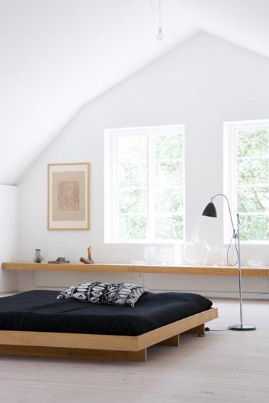 Pour la déco de cette chambre zen, juste un grand lit confortable en chêne clair recouvert d'un dessus lit noir pour contraster avec la pureté du blanc des murs et une longue étagère en chêne clair également. Une déco sobre pour une ambiance pleine de sérénité