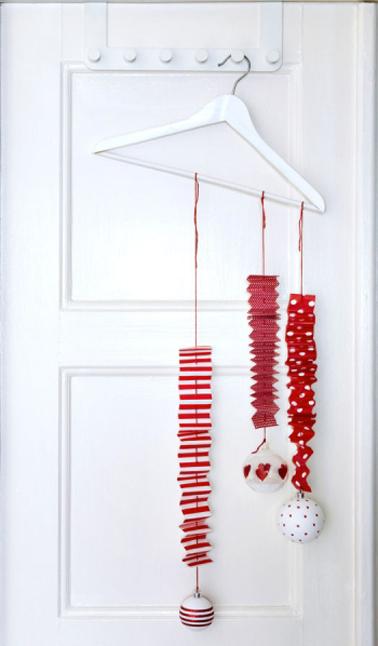 Une décoration de porte pour Noël originale en rouge et blanc réalisée avec des guirlandes de papier et des boules accrochées à un simple porte-manteau
