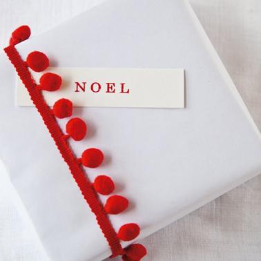 Pour faire des paquets cadeaux de Noël en rouge et blanc, du papier kraft blanc, bordé d'un ruban à pompons rouge et une étiquette imprimée en rouge pour personnaliser avec le prénom ou simplement Noël