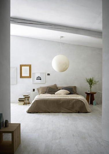 Déco d'une chambre zen avec une peinture grise sur les murs identique à la couleur du sol stratifié, linge de lit couleur taupe et chocolat