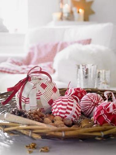 Pour un Noël en rouge et blanc récupérer les boules de l'an dernier et enrouler des bandes de tissu rouge et blanc, à compléter d'un ruban rouge pour les accrocher dans le sapin