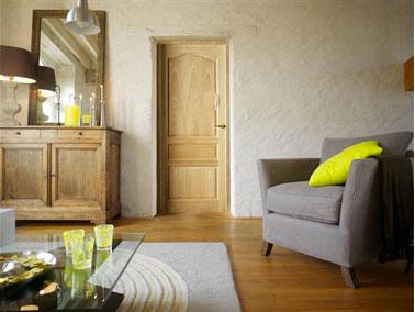 Un salon décoré autour de couleurs neutres et chaleureuses avec des murs et des textiles déclinés dans le même gris taupe de plusieurs valeurs,. Pour rehausser le tout , des touches de jaune vert acide pour le coussin et les objets de décoration