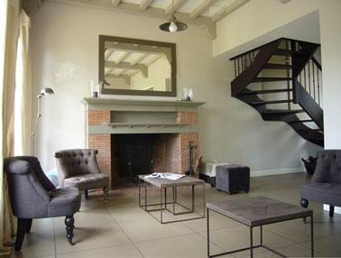 Déco d'un salon d'une maison de campagne où le gris est apporté par le mobilier et le gris anthracite de l'escalier. Peinture murale et double-rideaux couleur écrue