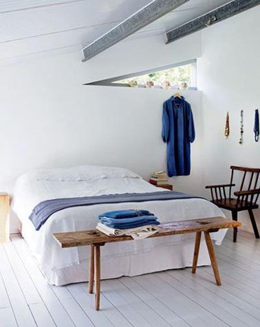 Peu de meubles, des touches de bleu pour une ambiance paisible dans une chambre blanche d'une maison de bord de mer