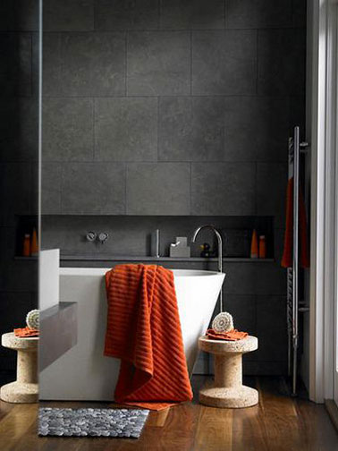 decoration design pour une salle de bain noir et blanche avec un carrealge mural gris anthracite et sa baignoire ilot blanche. le tout sur un superbe parquet chêne vitrifié