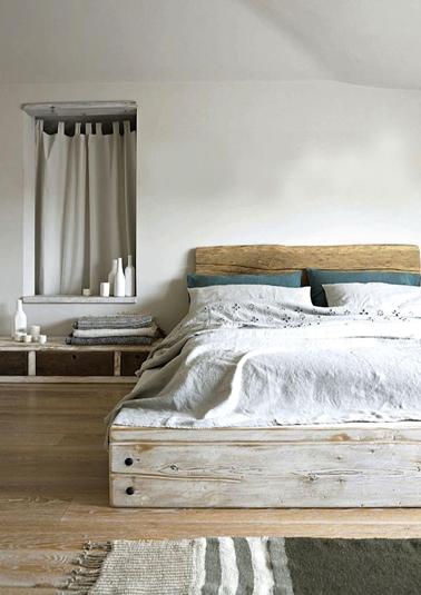 L'intimité d'une chambre grise sous mansarde rendue confortable avec un superbe lit en bois flotté fabriqué avec des planches de récup. La tête de lit est lasurée bois blond pour faire écho à la teinte du parquet bois