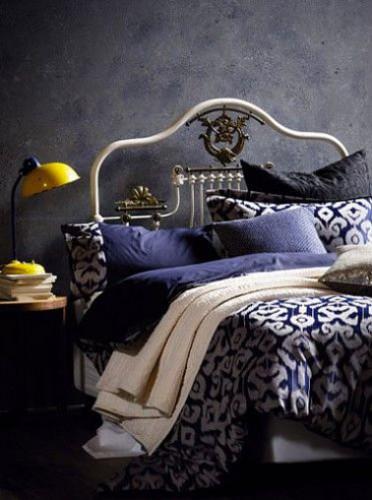 Douce harmonie couleur dans cette chambre d'adulte avec une peinture à effet violine et un linge de lit en dégradé de bleu et ivoire. La lampe de chevet rétro en jaune vif amène une touche  de couleur complémentaire heureuse