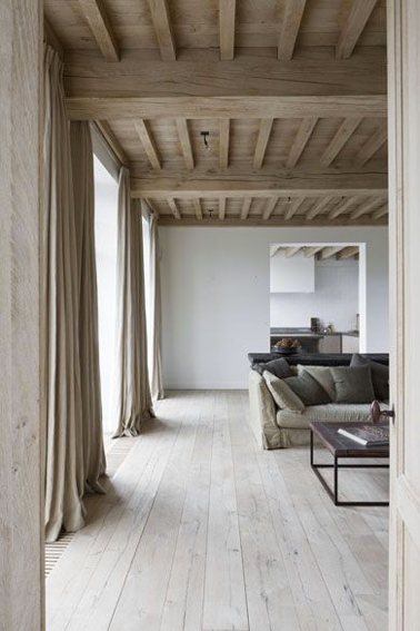 dans ce grand salon aux murs gris perle et au style épuré, la couleur lin des rideaux se cale ton sur ton avec la couleur du plafond plancher. Le sol en parquet chêne blanchi révèle l'aspect chaleureux du coin canapé décliné en dégradé de lin et gris.
