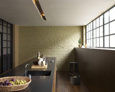 Murs de briques dans cuisine peint couleur ivoire et mis en valeur par le gris profond du soubassement et du plan de travail. Peinture couleur poivre et Ivoirine, collection Cuisine&Bain Dulux Valentine