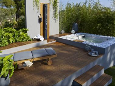 Déco terrasse zen avec bain de soleil et sol en bambou auprès de spa, un décor propice à la détente