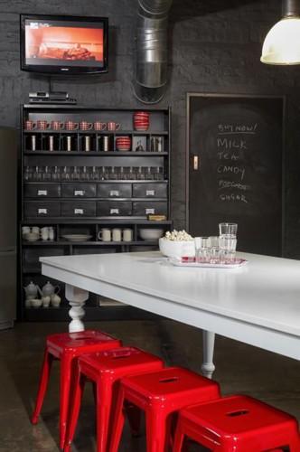 Un style retro chic pour une cuisine rouge et noir avec un vaisselier et des murs briques peints en noir satin noir et des tabourets Tolix rouge autour d'une table bois peinte en blanc laqué