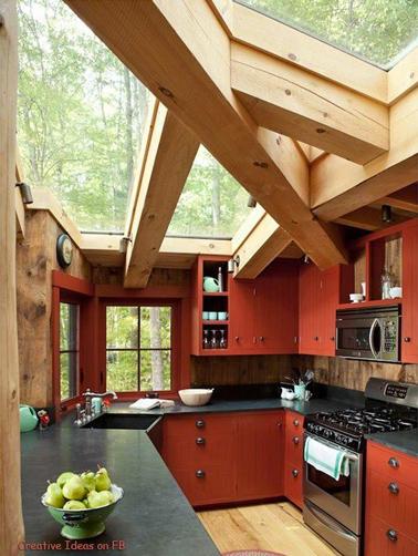 Sublime cuisine rouge et plan de travail gris anthracite installée dans une véranda face au jardin avec de grosses poutres bois et un toit en verre