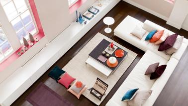 Dans un salon design, les encadrements de fenêtres peints en rose soulignent la teinte subtile de la peinture couleur lin sur les murs