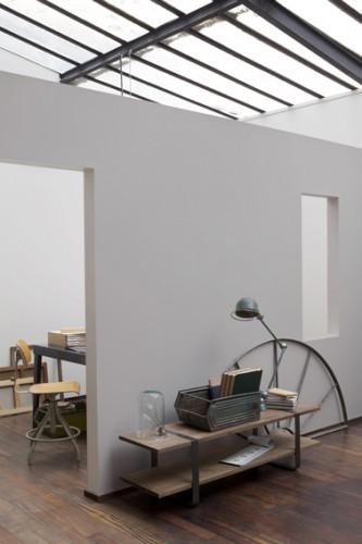 Une peinture salon de couleur grise en finition mate permet d'atténuer la lumière en provenance du toit verrière qui baigne le salon. Pour une déco salon esprit loft et chaleureuse, la peinture grise est associée à un sol parquet bois.  Couleur peinture : Collection inspiration industrielle, Univers Loft Chic chez Guittet.