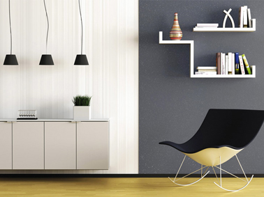 Dans un salon contemporain une peinture à paillettes grise sur un pan de mur mise en contraste avec le blanc mat de l'autre partie du mur. Pour un effet déco, suspensions et étagères noires et blanches sont positionnées en négatif