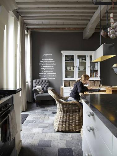 Dans une cuisine grise, un mur couleur taupe apporte une note chaleureuse autour du carrelage sol aux nuances de gris et noir et des meubles anciens repeints gris perle.