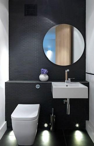 Design en noir en blanc pour une décoration WC avec du carrelage.  Sur le mur de la cuvette WC suspendu et du lave-main blanc un carrelage petits carreaux noir apporte un chic absolu à ces toilettes